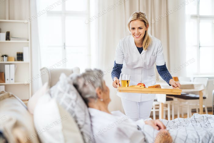 A health visitor bringing breakfast to a sick senior woman lying in bed at home.
