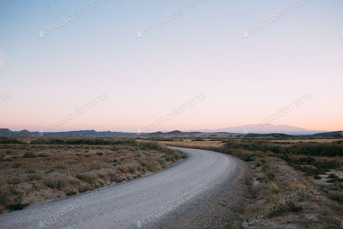 Empty gravel road in desert on sunset