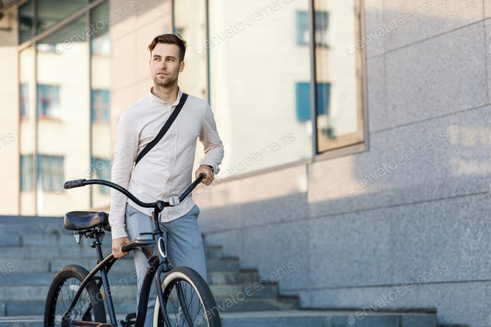 Convenient way to travel. Businessman in suit going to work by bike