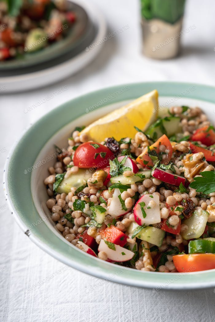 Close-up of two bowls with healthy vegan wholewheat pearl couscous salad with lemon