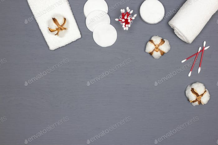 White terry towels, cotton pads and buds, cotton flowers. Copy space