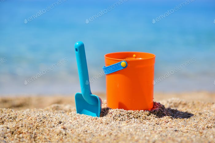 Bright plastic сhildren's beach toys on sand near sea. Summer vacation concept