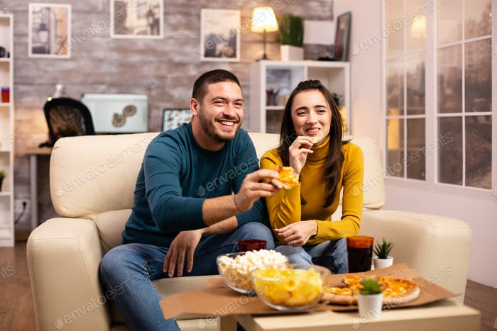 Beautiful young couple watching TV and eating fast food takeaway