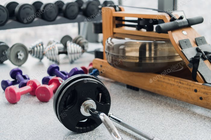 Weight plates and dumbbells on floor in gym, close up
