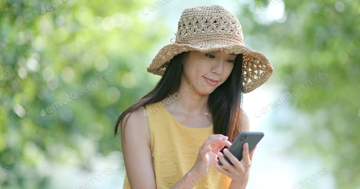 Woman wearing straw hat use of mobile phone at the park