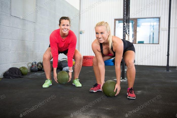 Determined Female Athletes Lifting Medicine Balls In Health Club