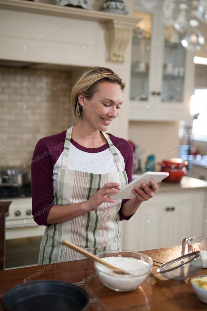 Woman using digital tablet while preparing cookies