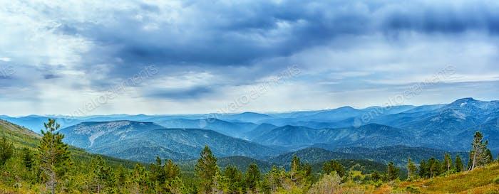 Cloudy sky over blue mountain range