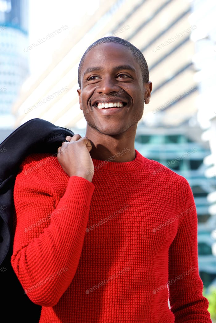 Smiling african man holding coat over shoulder in the city