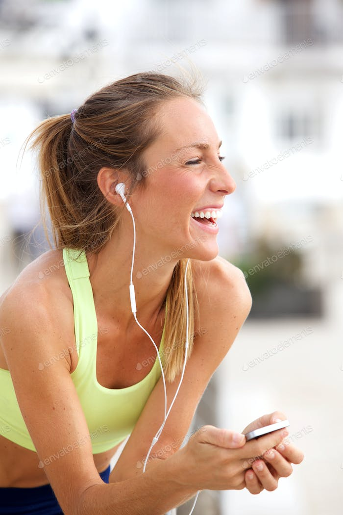 young woman listening to music with MP3 player and earphones