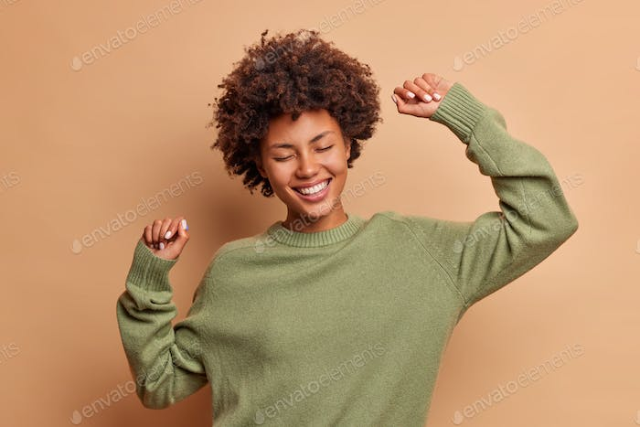 Horizontal shot of happy curly haired Afro American woman feels lively and dances carefree keeps arm