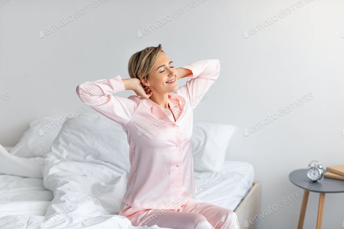 Peaceful woman stretching arms and back sitting on bed