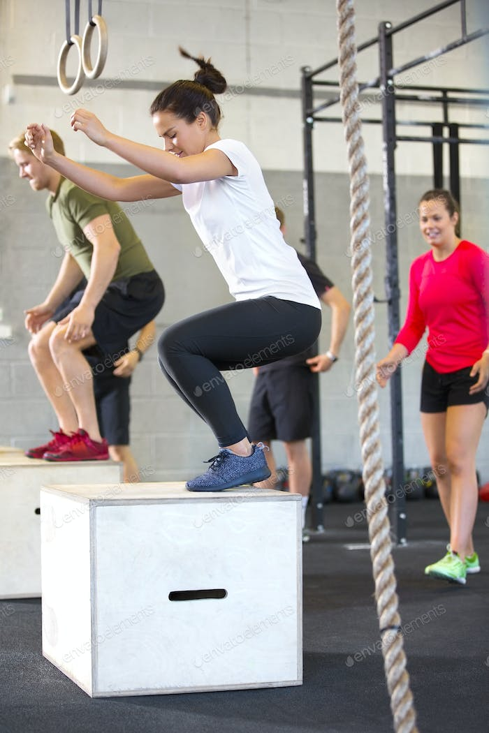 Determined Athletes Doing Box Jumping In Health Club