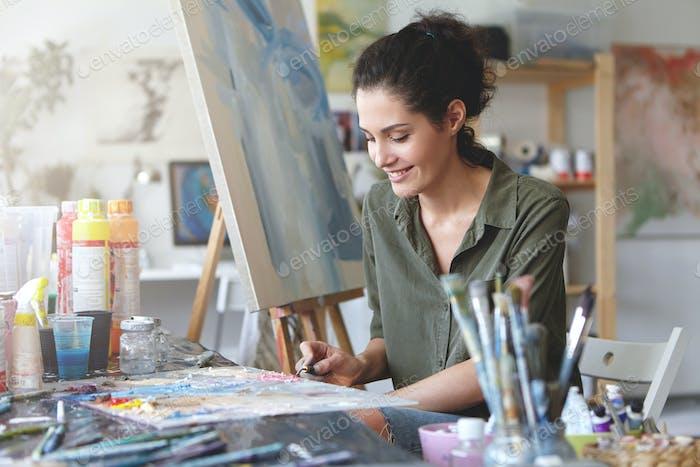 Bild einer niedlichen Künstlerin, die am Tisch sitzt, umgeben von Aquarellen und zeichnet etwas an