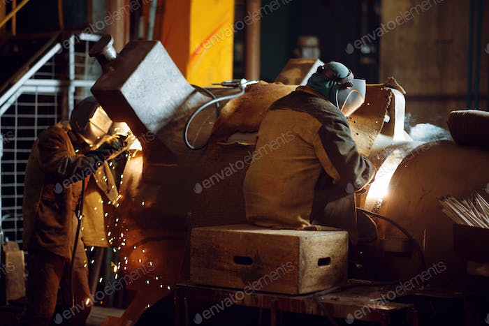 Two welder in masks works with metal, welding