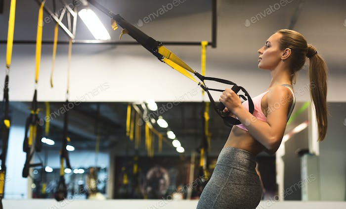 Young woman performing TRX training in gym, copy space