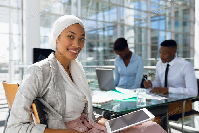 Businesswoman in hijab using digital tablet at desk in office