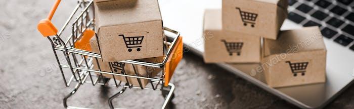 foto panorámica del carro de la compra de juguetes con pequeñas cajas de cartón cerca del ordenador portátil, concepto de comercio electrónico