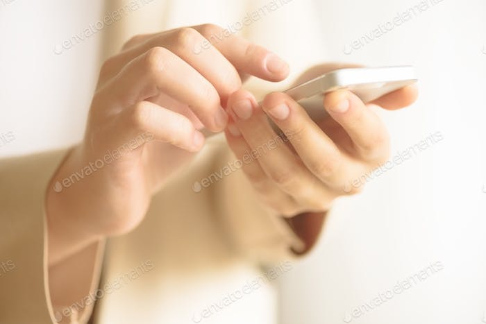 Businesswomen hand using smartphone on blur abstract background. Business, study, remote work