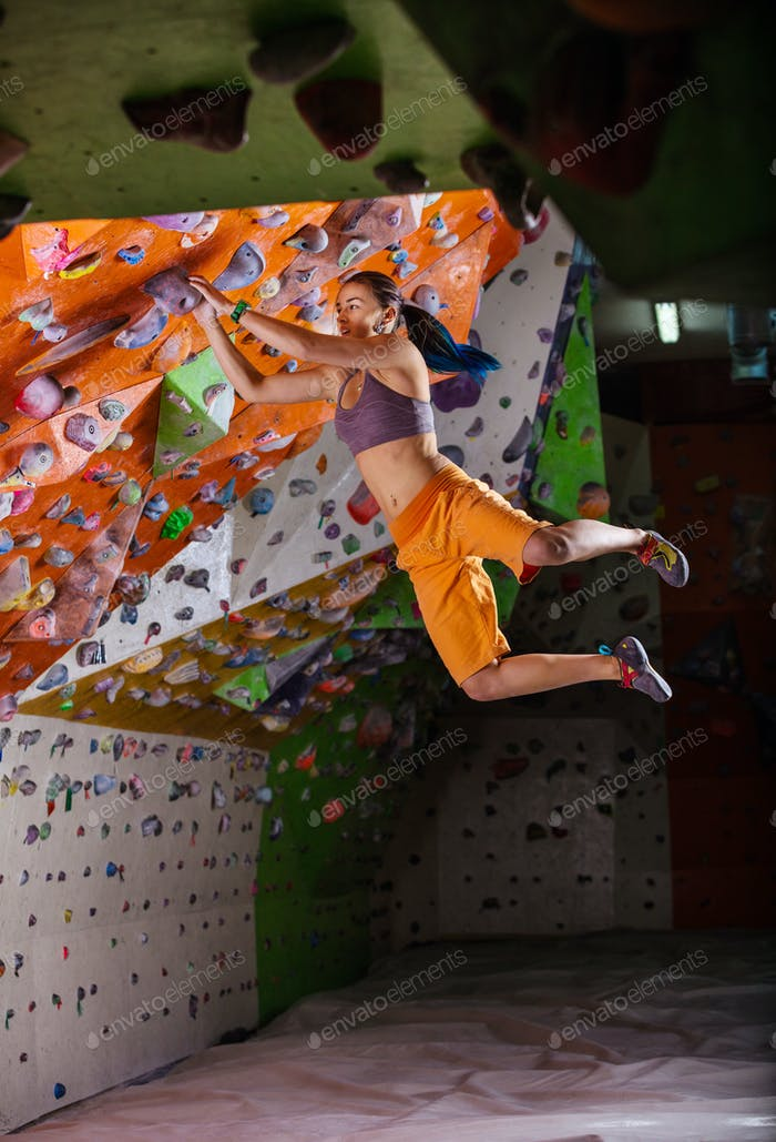 Young woman jumping on handhold while bouldering in climbing gym