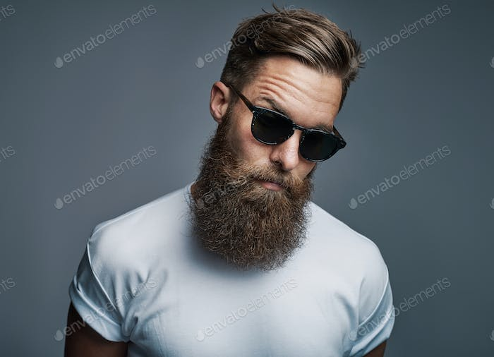 Stylish young hipster with a long beard wearing sunglasses