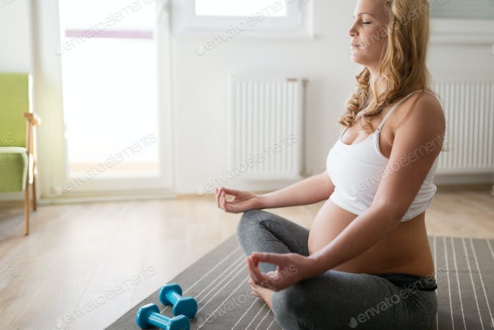 Pregnant woman relaxing and practicing yoga at home