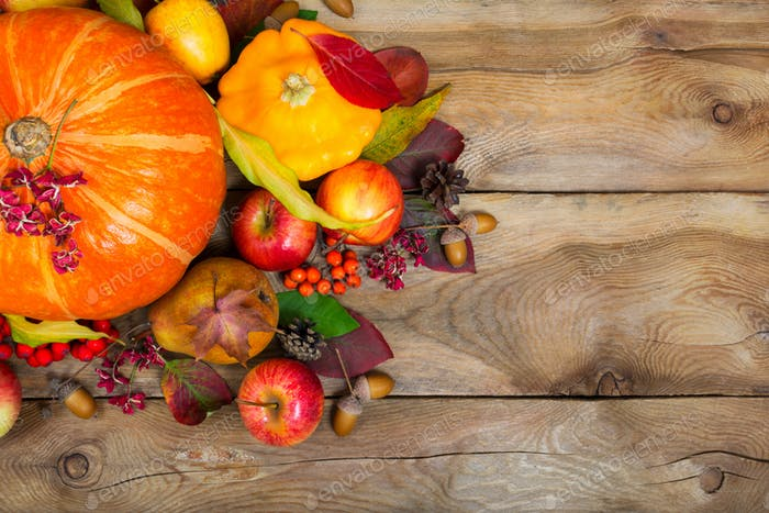 Thanksgiving background with pumpkin, yellow squash, apples, lea