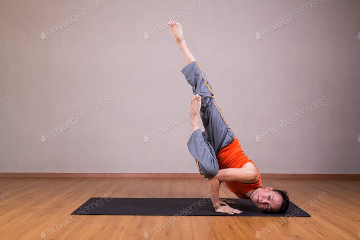 Man performs advanced yoga pose