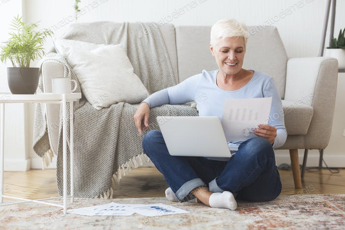 Old lady reading papers, sitting on floor with laptop