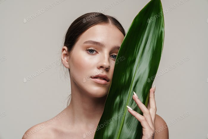 Image of seductive nice shirtless woman posing with green leaf