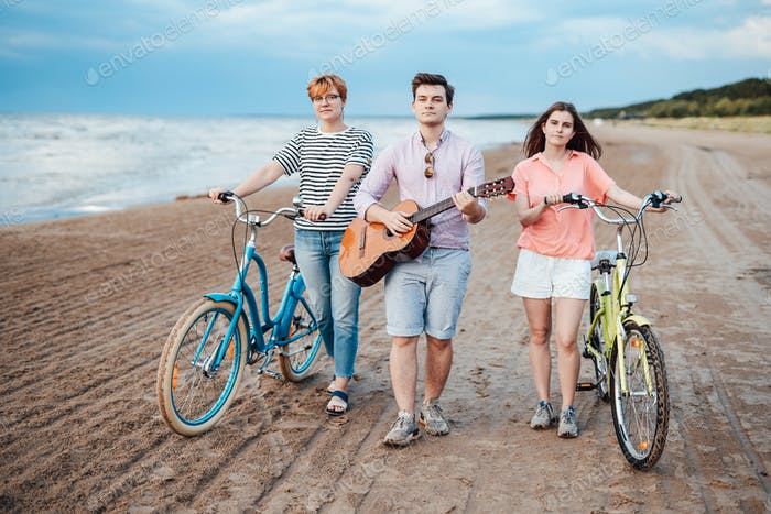 Mates walking on the beach with their bicycles