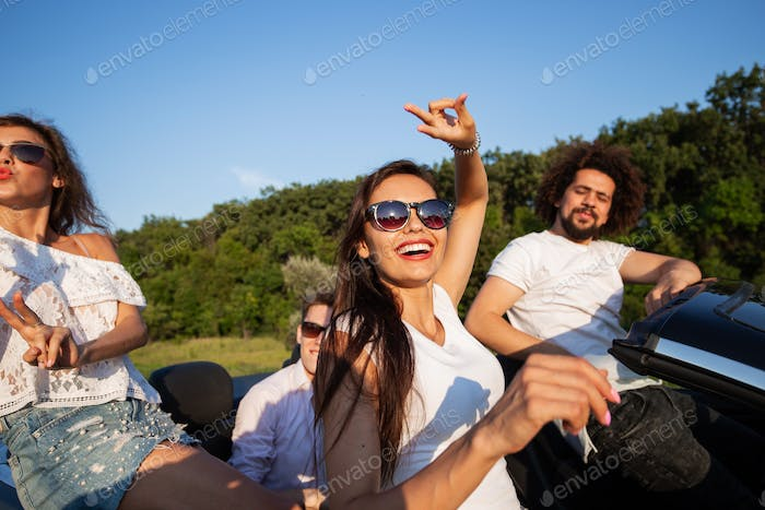 Charming young dark-haired woman in sunglasses with friends are sitting in a black cabriolet on a