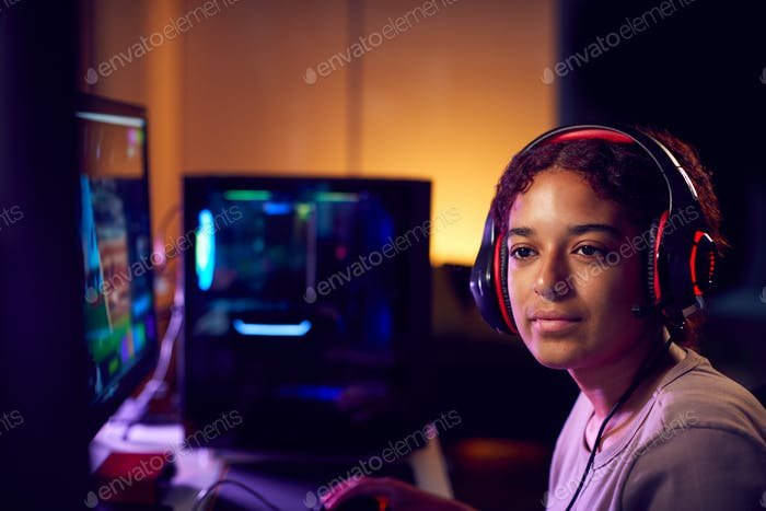 Teenage Girl Wearing Headset Gaming At Home Using Dual Computer Screens