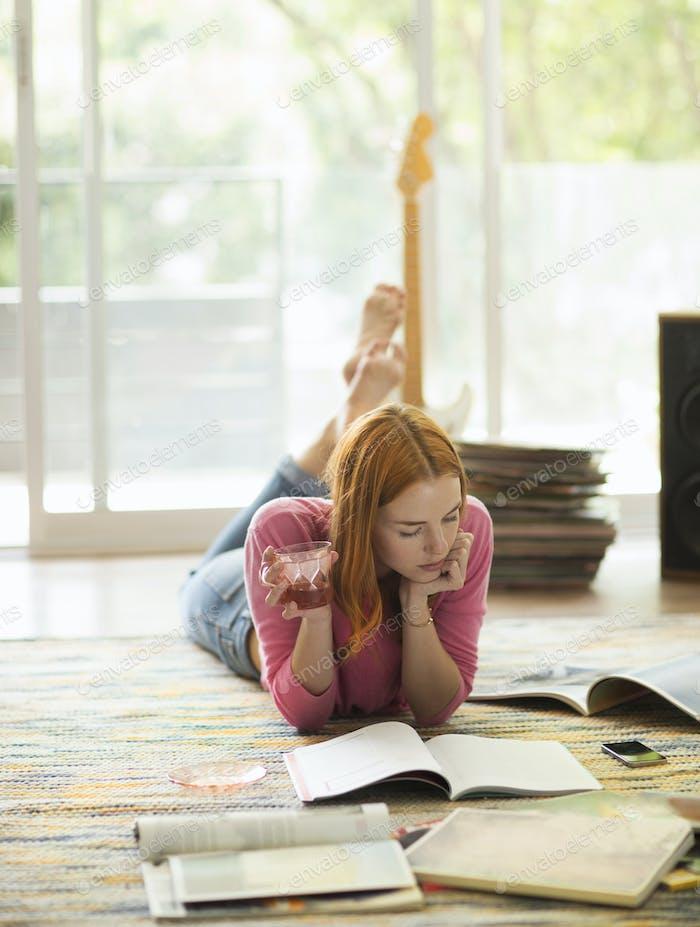 Eine Frau, die auf dem Boden liegt und ein Getränk hält und eine Zeitschrift liest.