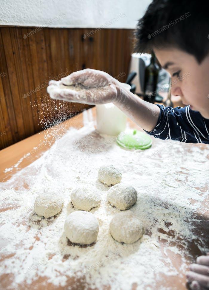Caucasian boy sprinkling flour over dough balls