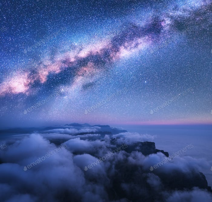 Milky Way over the low clouds and sea coast at starry night
