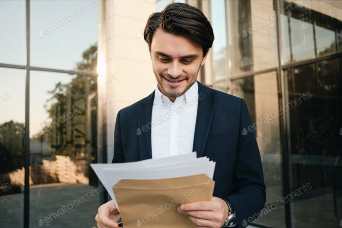 Young attractive smiling man in classic suit happily reading documents outdoors over glass building