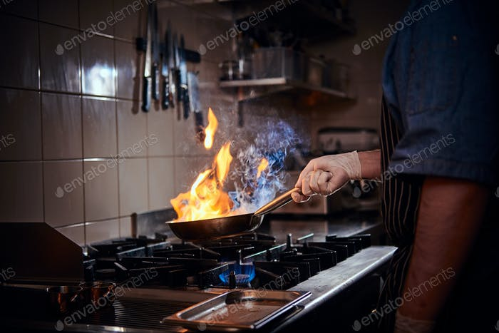 Cooker wearing gloves and apron frying flambe on a pan in a dark restaurant kitchen