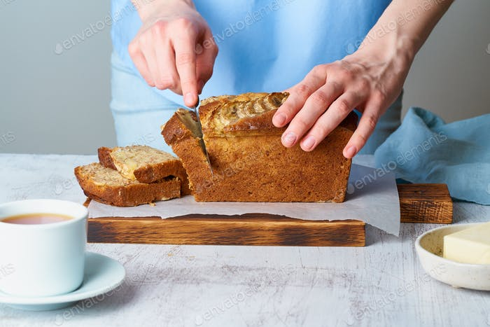 Woman cuts banana bread on a wooden board. Cake with banana