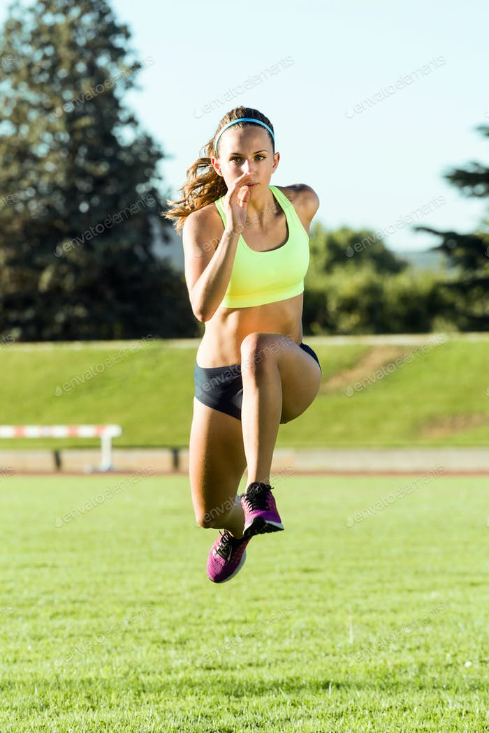 Fit young woman running on track field.