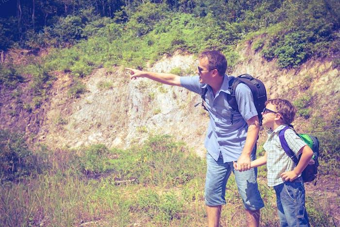 Vater und Sohn stehen in der Nähe des Teiches zur Tageszeit.