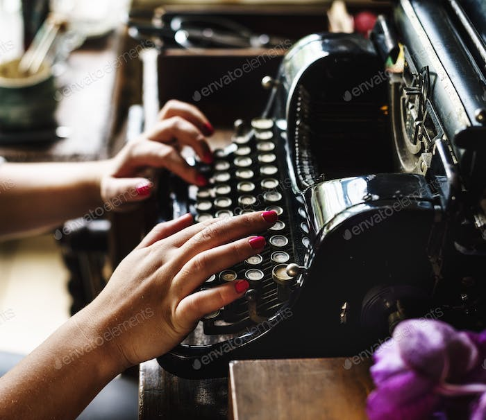 Woman typing vintage typewriter on wooden table