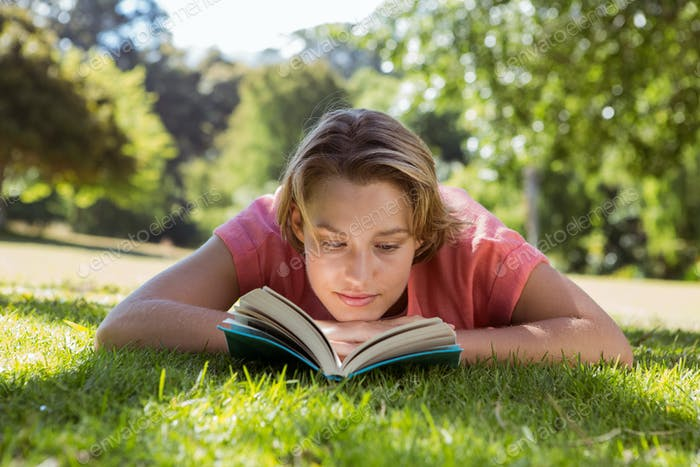 Pretty woman reading book in park on a sunny day