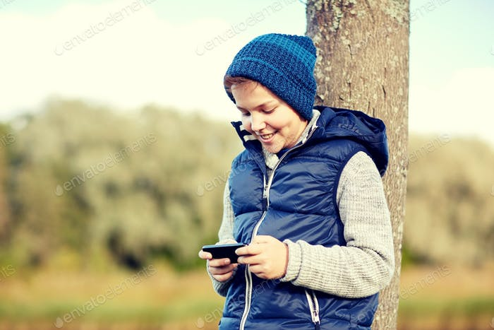 happy boy playing game on smartphone outdoors