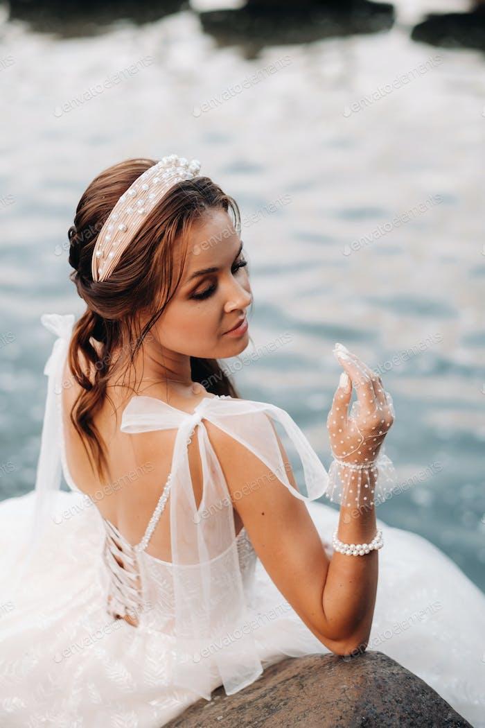 Eine elegante Braut in einem weißen Kleid, Handschuhen und nackten Füßen sitzt in der Nähe eines Wasserfalls im Park