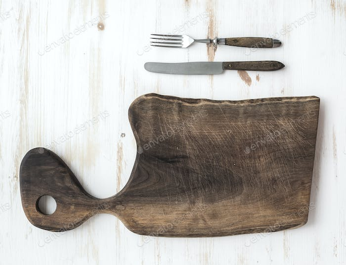 Kitchen-ware set. Old rustic chopping board made of walnut wood, knife, fork on a white background