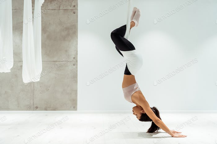 Sportive girl relaxing while practicing antigravity yoga and inversion position in yoga studio