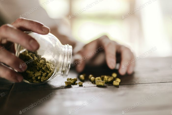 Male hand putting hops into jar