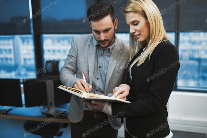 Secretary helping boss in office at workplace