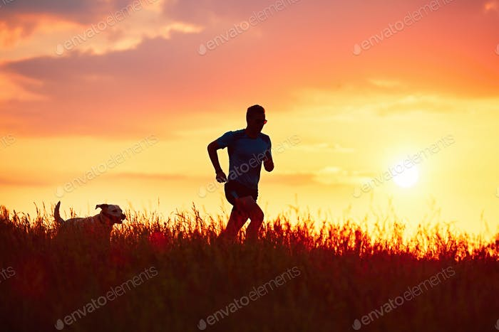 Athletic runner with dog at the sunset